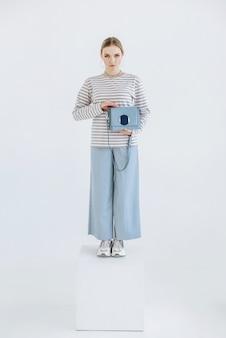 Jonge vrouw model poseren staande op kubus in witte kamer met tas in de hand?