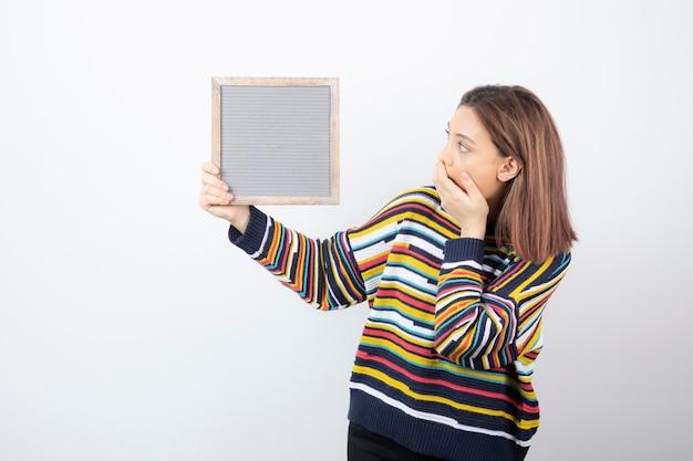 Jonge vrouw model staan en houden een frame.
