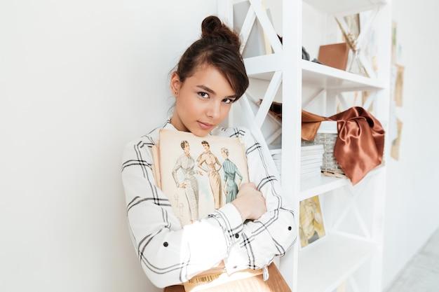 Jonge vrouw modeontwerper schetsboek houden