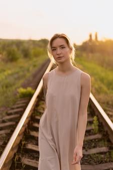 Jonge vrouw modieus portret met spoorweg op zonnige dag