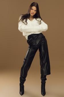 Jonge vrouw modieus poseren in studio, meisje model brunette op een beige achtergrond in lederen broek. hoge kwaliteit foto