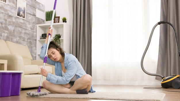 Jonge vrouw moe na het schoonmaken van de vloer met een dweil.