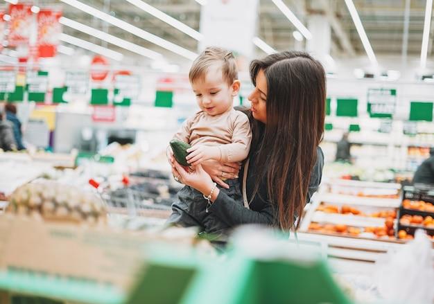 Jonge vrouw moeder met schattige baby jongen peuter kind op handen koopt de verse avocado in de supermarkt