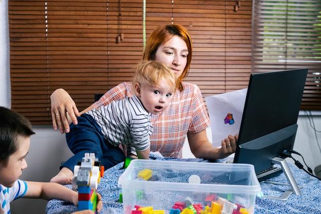 Jonge vrouw moeder probeert te werken op een computer op afstand werk tijdens de periode van zelfisolatie in verband met de coronavirus pandemie, soft focus.