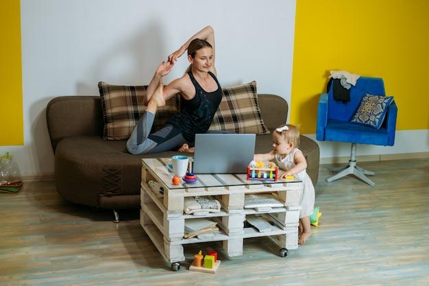 Jonge vrouw moeder zit op de bank met haar baby peuter dochter thuis yoga oefeningen te doen kijken
