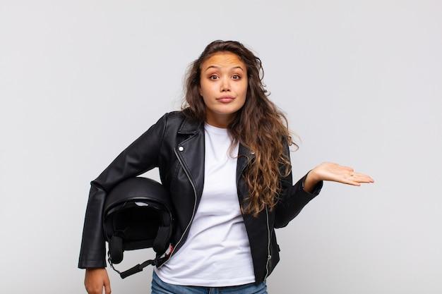 Jonge vrouw motorrijder die zich verbaasd en verward voelt, twijfelt, weegt of verschillende opties kiest met grappige uitdrukking