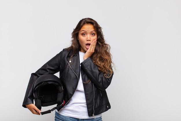 Jonge vrouw motorrijder geschokt en bang, doodsbang op zoek met open mond en handen op de wangen