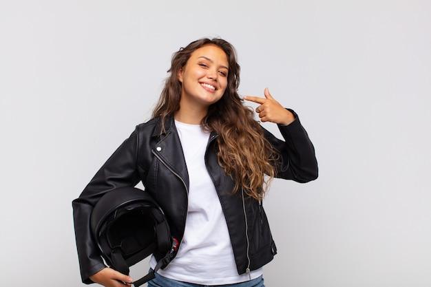 Jonge vrouw motorrijder glimlachend vol vertrouwen wijzend naar eigen brede glimlach, positieve, ontspannen, tevreden houding
