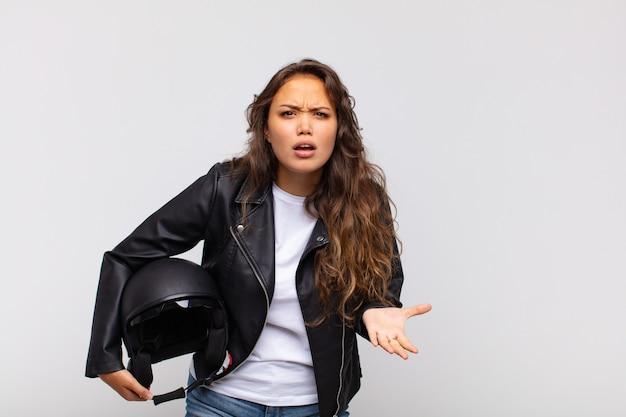 Jonge vrouw motorrijder kijkt boos, geïrriteerd en gefrustreerd schreeuwend wtf of wat is er mis met jou