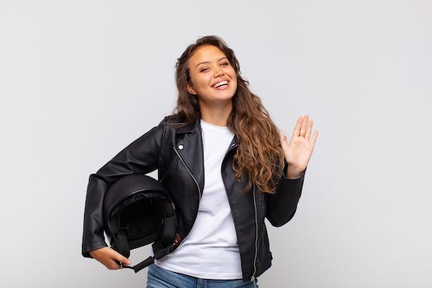 Jonge vrouw motorrijder lacht vrolijk en vrolijk, zwaait met de hand, verwelkomt en begroet je, of neemt afscheid