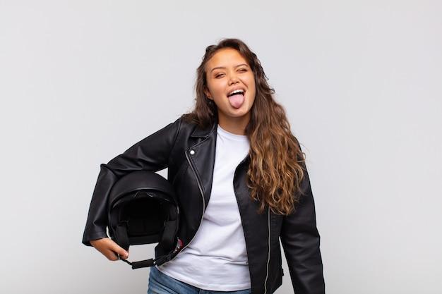 Jonge vrouw motorrijder met vrolijke, zorgeloze, rebelse houding, grapje en tong uitsteekt, plezier maken