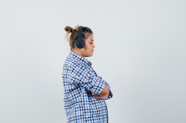 Jonge vrouw muziek luisteren via koptelefoon in geruit overhemd en geconcentreerd kijken.