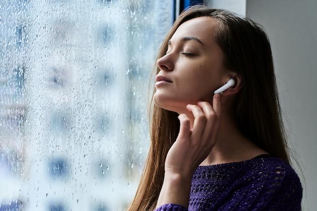 Jonge vrouw muziekliefhebber met gesloten ogen in draadloze oordopjes geniet en luistert naar rustgevende kalmerende ontspannende muziek tijdens het staan bij het raam met regendruppels in regenachtig herfstweer