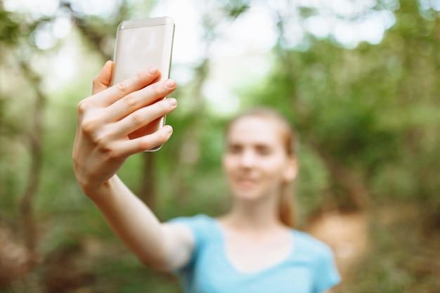 Jonge vrouw na een ochtend joggen neemt een selfie aan de telefoon