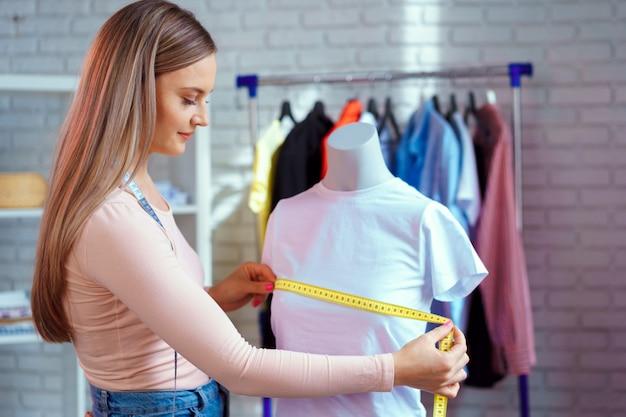 Jonge vrouw naaister metingen met etalagepop