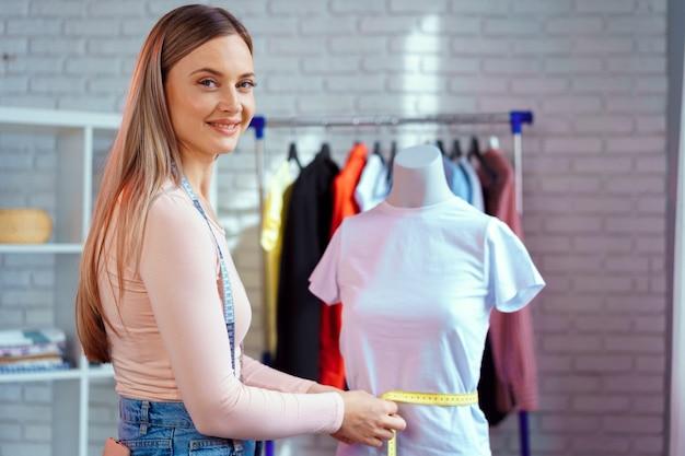 Jonge vrouw naaister metingen met mannequin in haar kantoor