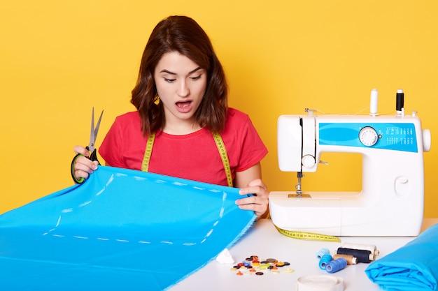 Jonge vrouw naaister naaien in haar atelier, gefrustreerd omdat ze een fout maakt, zittend met geopende mond