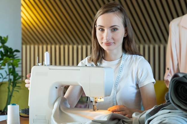 Jonge vrouw naaister naait op een naaimachine zittend aan een tafel