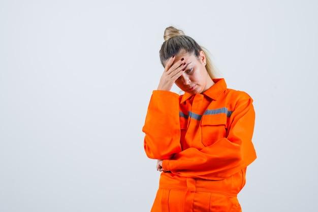 Jonge vrouw naar beneden kijken terwijl hand op het hoofd in uniform werknemer en op zoek boos. vooraanzicht.