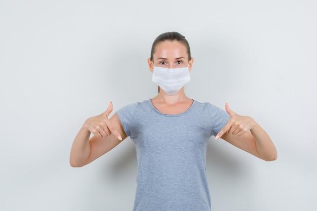 Jonge vrouw naar beneden wijzend in grijs t-shirt, masker vooraanzicht.