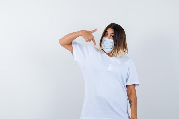Jonge vrouw naar beneden wijzend in t-shirt, masker en op zoek naar zelfverzekerd, vooraanzicht.