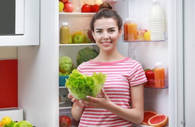 Jonge vrouw naast koelkast, close-up