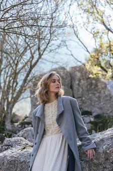 Jonge vrouw naast rotsen staren