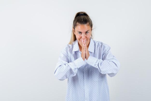 Jonge vrouw namaste gebaar in wit overhemd tonen en gelukkig kijken