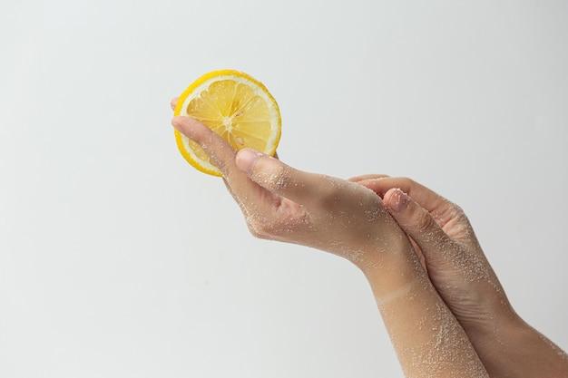 Jonge vrouw natuurlijke citroen scrub toe te passen op handen tegen wit oppervlak