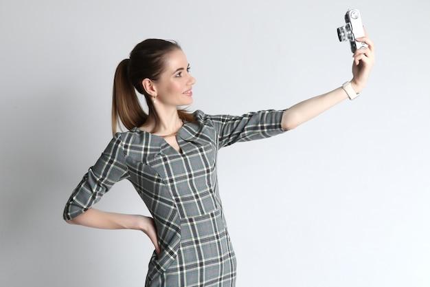 Jonge vrouw neemt een selfie met behulp van een vintage camera vanuit de bovenste hoek