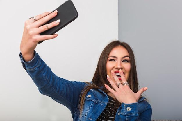 Jonge vrouw neemt een selfie met smartphone