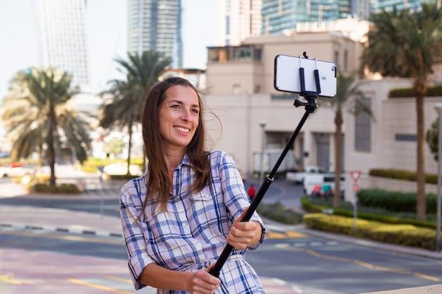 Jonge vrouw neemt een selfie tegen de achtergrond van wolkenkrabbers en palmbomen