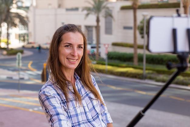 Jonge vrouw neemt een selfie tegen de achtergrond van wolkenkrabbers