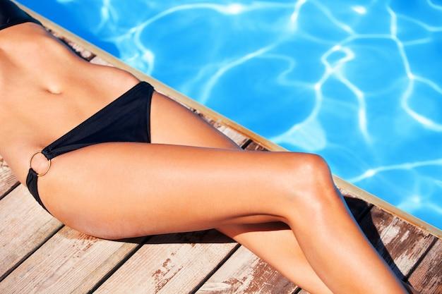 Jonge vrouw neemt een zonnebad bij het zwembad