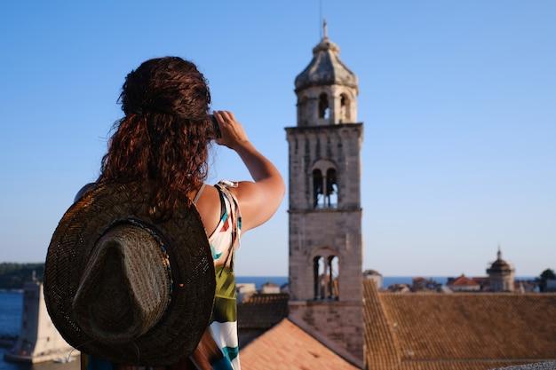 Jonge vrouw neemt foto op de stadsmuren van de oude stad dubrovnik, kroatië