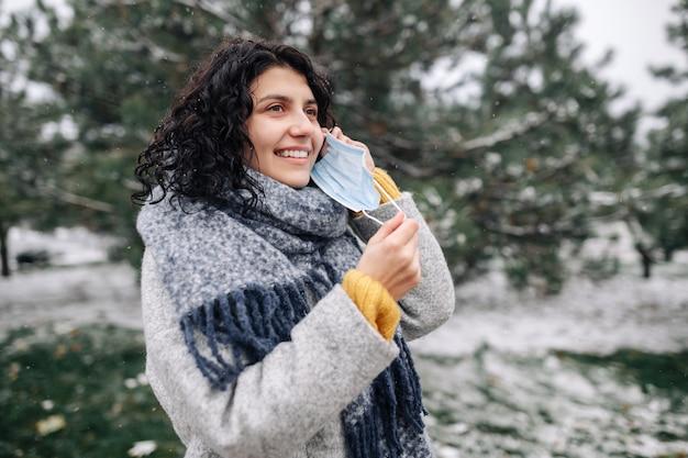 Jonge vrouw neemt het medisch steriele masker over in een winters sneeuwpark op een koude ijzige dag.
