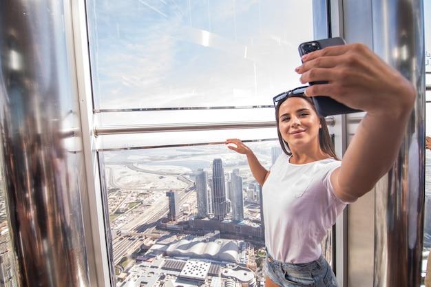 Jonge vrouw neemt selfie aan de telefoon tijdens een wandeling op de top de burj khalifa