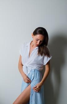 Jonge vrouw neerkijkt en poseren vooraan in wit t-shirt en lichtblauwe rok en ziet er charmant uit