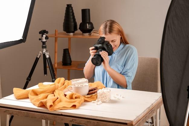 Jonge vrouw nemen foto van drankje met marshmallows in professionele studio