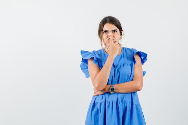Jonge vrouw neus met vinger in blauwe jurk aan te raken en peinzend op zoek