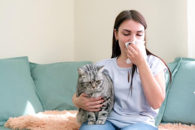 Jonge vrouw niest van bontallergie op de bank en speelt met haar kat.
