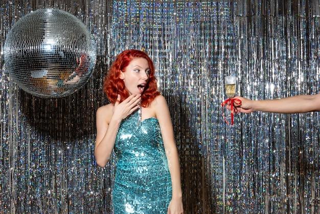 Jonge vrouw nieuwjaar vieren in feest en champagne nemen op glanzende gordijnen