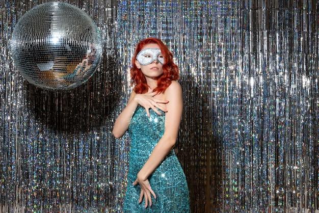 Jonge vrouw nieuwjaar vieren in masker op glanzende gordijnen