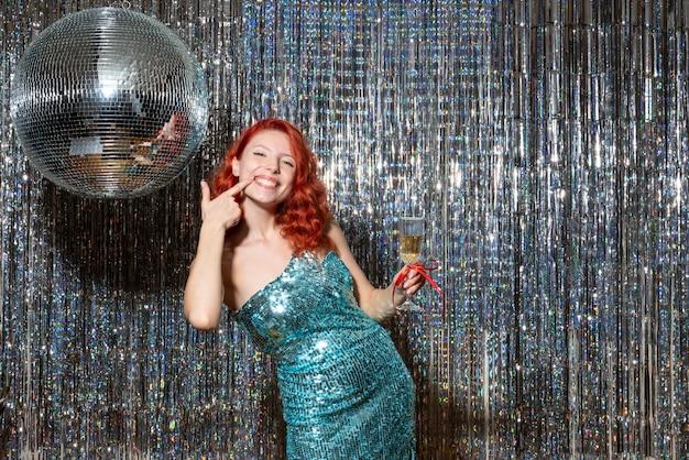 Jonge vrouw nieuwjaar vieren in partij in mooie jurk op glanzende gordijnen
