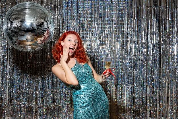 Jonge vrouw nieuwjaar vieren in partij in mooie jurk op lichte gordijnen