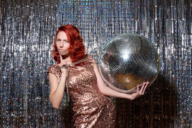 Jonge vrouw nieuwjaar vieren in partij met disco bal op heldere gordijnen gordijnen