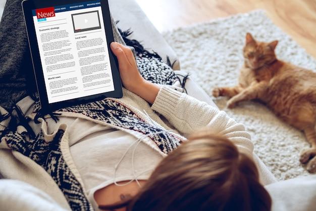 Jonge vrouw nieuws lezen met behulp van tablet zittend op de bank thuis