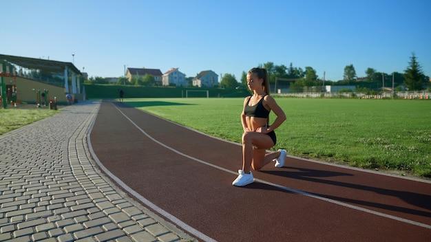 Jonge vrouw oefent lunges in het stadion