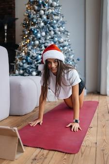 Jonge vrouw oefent online oefeningen met een trainer