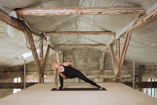 Jonge vrouw oefent yoga op een verlaten bouwplaats